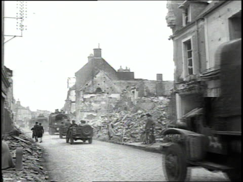 June 1944 MONTAGE trucks and Jeeps filled with US Army soldiers driving through damaged town as soldiers march along the side / Normandy France