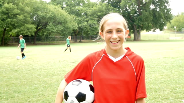 Junior High school age female soccer player tossing ball on sidelines during game