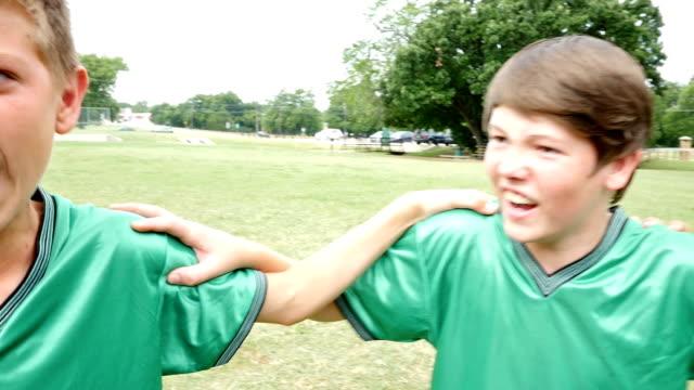 Junior high school soccer team huddled before game on field