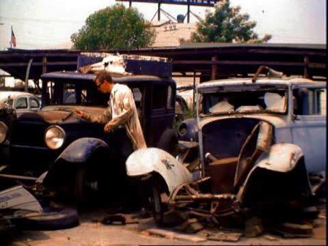 Junked early 1940s Packard being waxed by hand in junkyard / man wearing dirty frock coat walking through auto junkyard tossing aside debris on old...