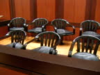 A jury box contains fourteen empty black chairs in a courtroom in the Queens County Criminal Courts Building in Queens New York