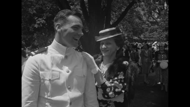Just graduated midshipman his mother standing next to him / just graduated midshipman walking with bride after wedding down steps under arch of...