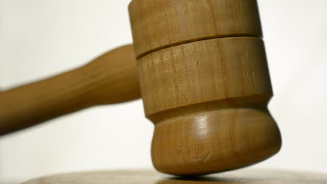 Justice. A wooden gavel striking a sounding block.