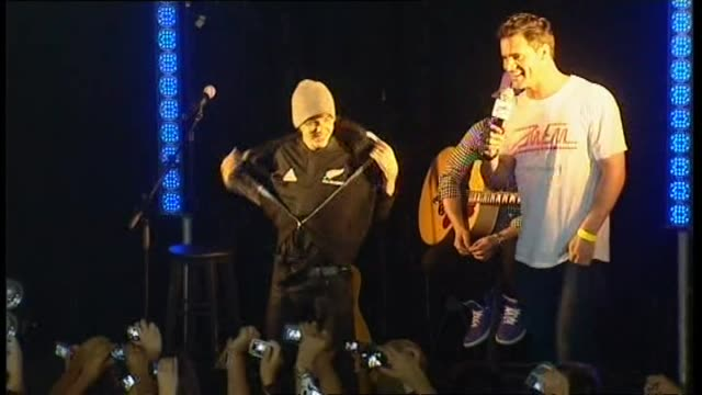 Justin Bieber being introduced on stage removing jumper to reveal he is wearing replica All Blacks rugby jersey and speaking about bungee jumping...
