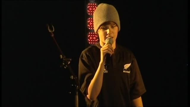 Justin Bieber wearing All Blacks replica jersey on stage speaking to cheering students about bungee jumping during visit to Strathallan College in...