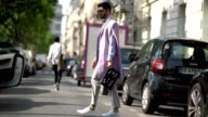 Kadu Dantas wears sunglasses a pink sleeveless blazer jacket a striped shirt a black bowtie a clutch gray pants and white sneakers outside the...