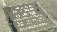 Kanji characters and numerals on a plaque provide the nautical coordinates for Higashi-Kojima in Okinotorishima Island, Japan.