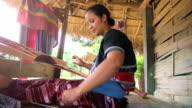 Karen women talking on the mobile phone while weaving