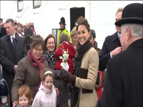 Kate Middleton accepts flowers as she and her fiancee Prince William embark on a walkabout during their first official visit together in Anglesey