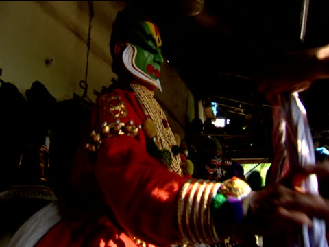 Kathakali dancer wearing face paints getting into ornate costume Kochi India