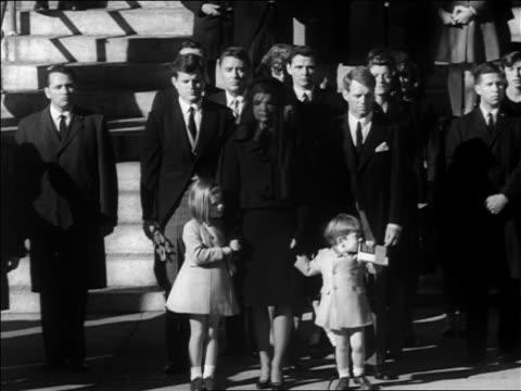 Kennedy family standing outdoors at JFK's funeral / tilt down John Jr salutes / newsreel