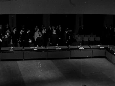 Kennedy's visit Parid NATO and SHAPE visits FRANCE Paris NATO building flags on poles Kennedy and others into chamber Kennedy seated at desk United...