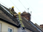 emergency services in Folkestone Firemen up ladders removing damaged chimney pots from rooftops / More of damaged chimney stacks rubble on pavements