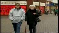 Kettering High Street with shoppers along ENGLAND Kettering EXT High street with shoppers along / woman pushing toddler in pushchair towards camera /...