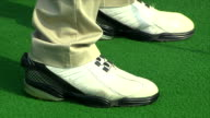Khaki pants hem draping onto golf shoes standing in set up stance on artificial turf w/ shadow of club by shoe shadow moving forward right foot...