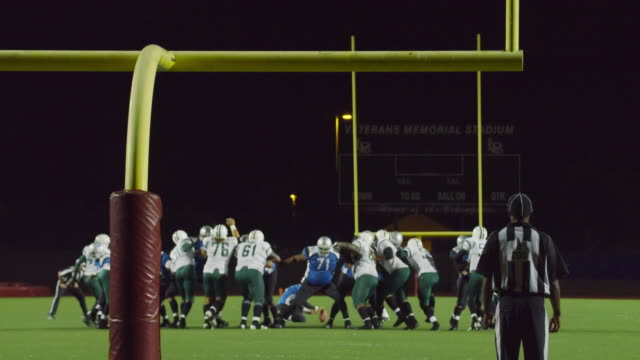 WS SLO MO. Kicker kicks wide of uprights and defending team celebrates as referees signal missed field goal in professional football game.