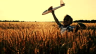 SLO MO Kid running with airplane toy in wheat field