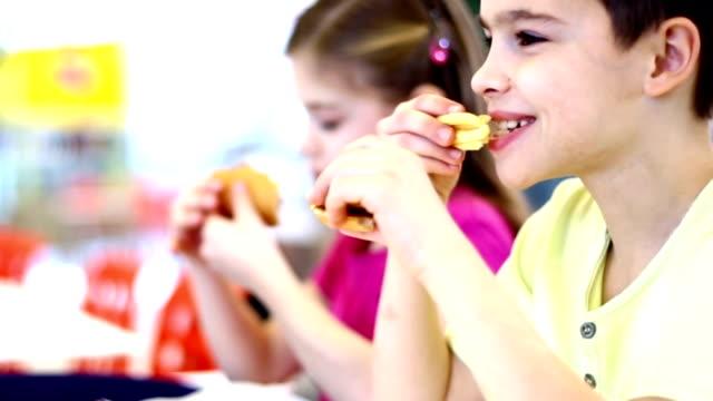Kinder essen von Burgern und Pommes Frites.