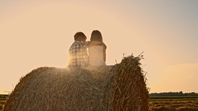 WS Kinder umarmen auf hay Heuballen bei Sonnenuntergang