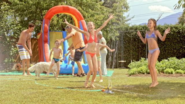 SLO MO kinderen genieten van een tuinfeest op een hete zomerdag