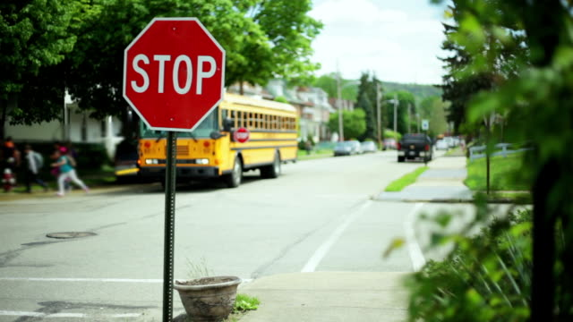 Kids get of school bus next to stop sign