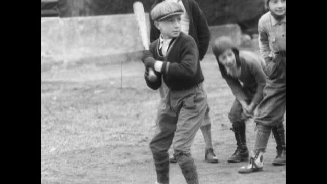 kid's go hand over hand up the side of a baseball bat to decide who is up to bat first / children pitching and hitting baseball during game /...