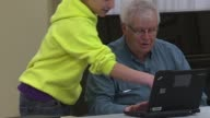 Kids Helping Senior Citizens Use Laptop Computers in Chicago on March 18 2015