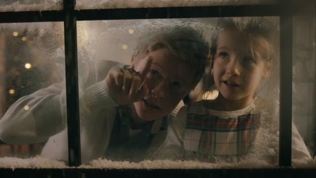 Kinder mit Blick auf die verschneite Fenster