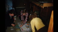 1956 HOME MOVIE Kids on floor playing game of Monopoly / Toronto, Canada