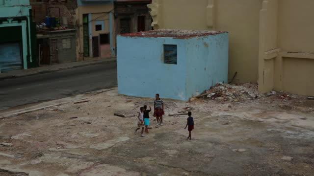 kids playing baseball in empty lot cuba