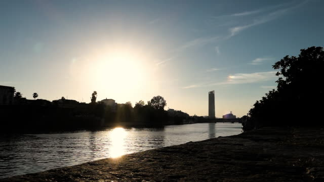 Kids sillhouette jumping in guadalquivir river in sevilla in slowmotion