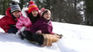 Kids sledding on snowy hill