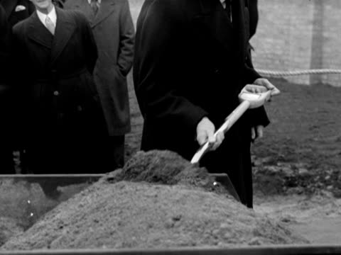 King George VI helps to plant a tree at the new Lansbury housing estate in Poplar