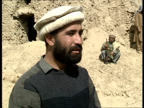 01 Intv Tahir Khan Mujaheddin leader Mujaheddin seated in back of van and wind in their headress GV of outcrop of damaged housesTravelling shots...
