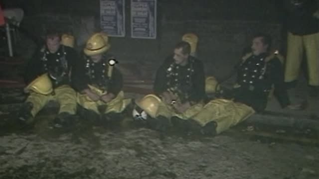 King's Cross fire 30th anniversary approaches AS191187019 / TX Tired firemen sitting on ground Firefighters in breathing gear along END LIB
