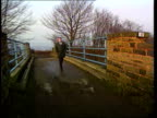 Nr Barnsley MS Plain clothes policeman across bridge towards TGV Railway lines and winter trees on either side TMS Embankment down side of railway...