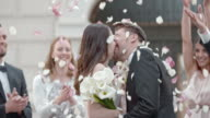 SLO MO Kissing newlyweds being showered with rose petals