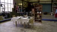 Kitchen furniture and dishes break during an earthquake simulation in a warehouse. Available in HD.