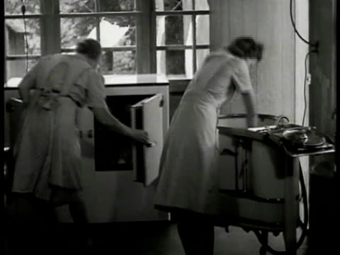 Kitchen w/ woman opening freezer other woman moving wash into next section of machine elder woman moving wrapped package from one side of freezer to...
