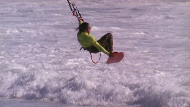Kite surfer is lifted up to perform mid-air twist and then drops back onto water Available in HD.
