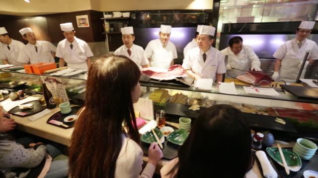 Kiyoshi Kimura president of Kiyomura K K third right cuts a tuna as sushi chefs and customers applaud at a Sushi Zanmai sushi restaurant in Tokyo...