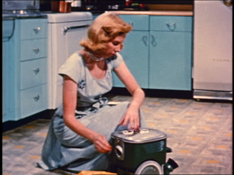1950 kneeling blonde woman in kitchen wrapping power cord around vacuum cleaner