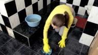 kneeling pregnant woman cleans the bathroom