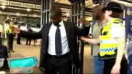 British Transport Police search commuters More of commuters passing through portable metal detector and police using hand held detector to search...