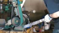 Knife maker grinding down edges on blade
