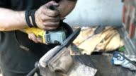 Knife maker gringind down edges on blade