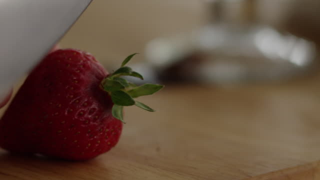 Knife slices off top of strawberry on wooden cutting board