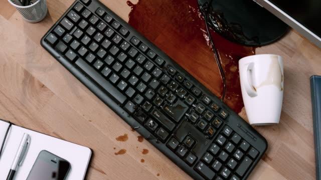 SLO MO LD kloppen over een kopje koffie met een notebook en het morsen op het computertoetsenbord