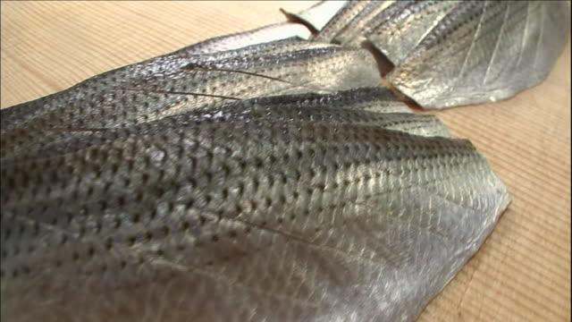 Kohada fillets lie on a cutting board in a sushi restaurant.