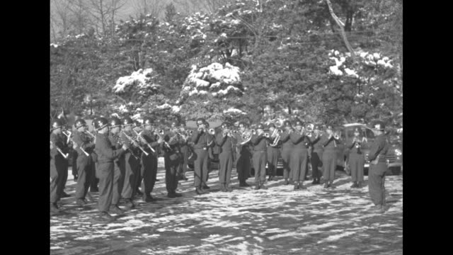 VS Korean Army band musicians play in a snowy area with trees behind them on the grounds of South Korean President Syngman Rhee's residence conductor...